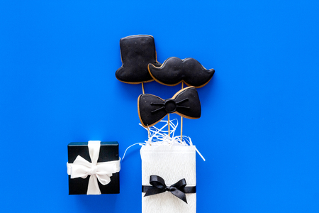 Happy Fathers day cards. Black tie, mustache and hat cookies and gift. Blue top view copyspace