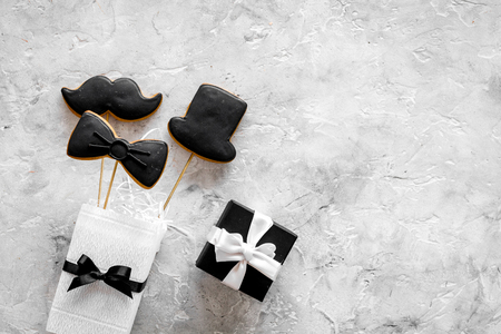 Birthday gift for men. Wrapped box, cookies in shape of black tie, mustache, hat. Grey top view copyspace