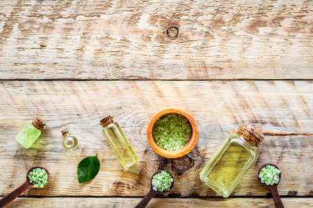 Spa salt and lotions for skin with tea tree oil on rustic wooden top view pattern copyspace Stock Photo
