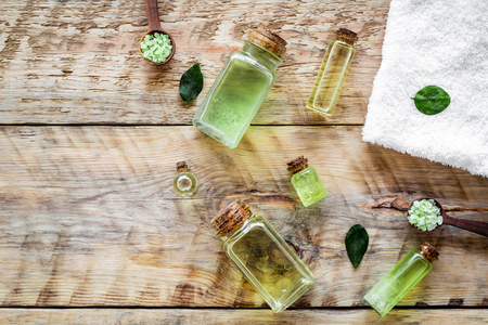 Skin care products with tea tree oil in bottles on rustic wooden top view pattern copyspace