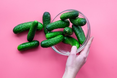 Hand takes fresh cucumbers in bowl on pink top view Stock Photo - 88942276