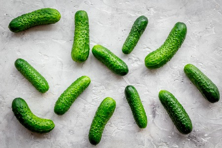 Fresh cucumbers on grey background top view