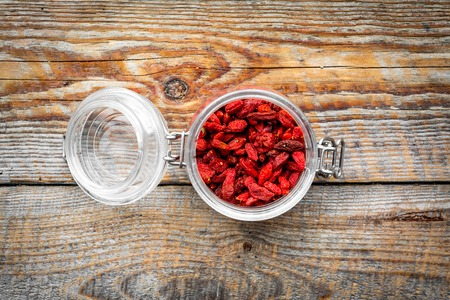 Dried goji berries in glass jar on wooden background top view copyspace Banco de Imagens
