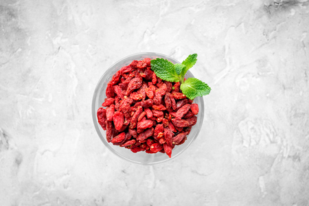 Dried goji berries in glass jar on grey background top view copyspace Imagens