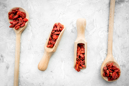 Wooden spoons with dried goji berries on grey background top view Stock Photo