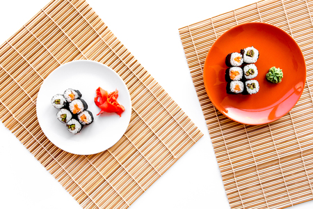 Sushi roll with salmon and avocado on plate with soy sauce, chopstick, wasabi on mat. White background Top view