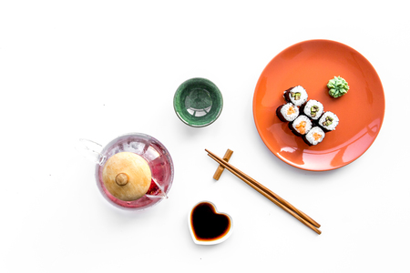 Sushi roll with salmon and avocado on plate with soy sauce, chopstick, wasabi on white background top view copyspace Stock Photo