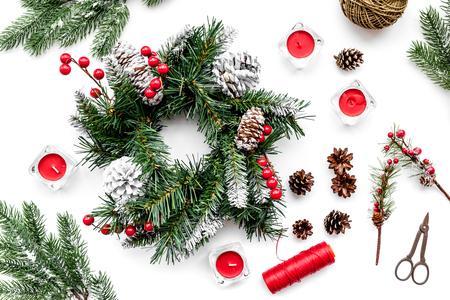 Machen Sie Weihnachtskranz. Fichtenzweige, Kegel, Threads, Sciccors auf weißer Draufsicht Standard-Bild - 88969575