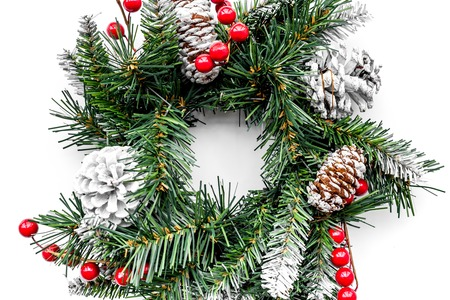 Christmas wreath woven of spruce branches with red berries on white top view