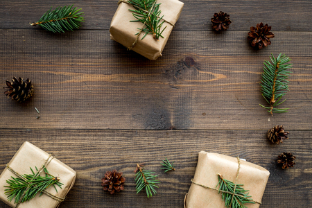 Gifts for new year wrapped in craft paper near spruce branches and cones on wooden top view pattern copyspace