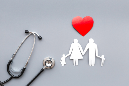 Take out health insurance for family. Stethoscope, paper heart and silhouette of family on grey top view Stock Photo