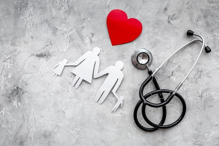 Take out health insurance for family. Stethoscope, paper heart and silhouette of family on grey stone top view