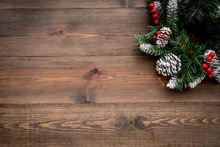 Weihnachtskranz gesponnen von den Fichtenzweigen mit roten Beeren auf Draufsichtspottbild des hölzernen Hintergrundes Standard-Bild - 88906908