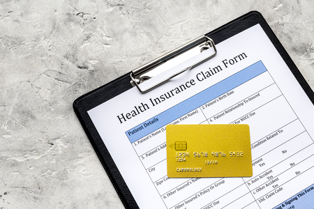 Buy health insurance. Document, pad, pen and bank card on grey background top view Stock Photo