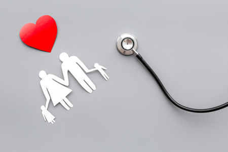 Take out health insurance for family. Stethoscope, paper heart and silhouette of family on grey background top view