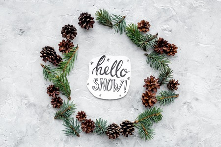 Hello snow hand lettering. Winter pattern with spruce branch and cones on grey background top view