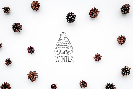 Hello Winter hand lettering with hat. Winter pattern with pinecones on white top view