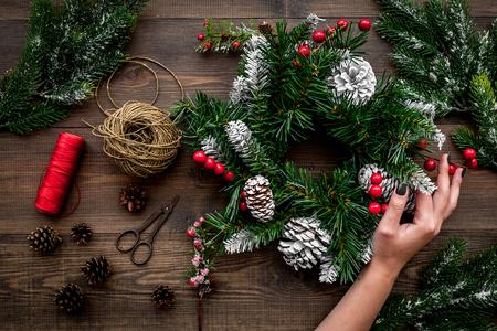 Weihnachtskranz machen. Übergeben Sie Grifffichtenzweige, Kegel, Threads, Sciccors auf hölzerner Draufsicht Standard-Bild - 88943000