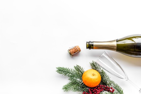 New year eve. Spruce branch, glasses, champagne bottle, tangerines on white top view copyspace