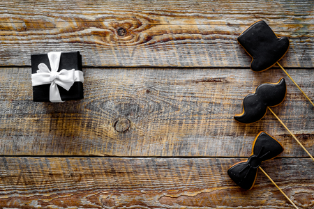 Birthday gift for men. Wrapped box, cookies in shape of black tie, mustache, hat. Wooden top view copyspace Stock Photo