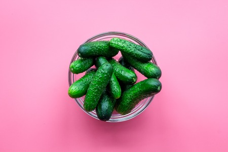 Fresh cucumbers in bowl on pink top view copyspace