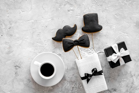 Birthday gift for men. Wrapped box, cookies in shape of black tie, mustache, hat. Grey top view
