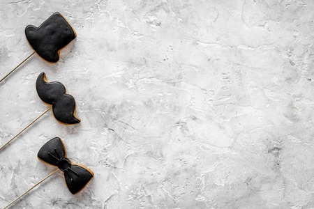 Men birthday concept. Set of cookies in shape of black tie, mustache and hat. Grey stone top view copyspace Stock Photo