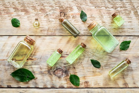 Skin care products with tea tree oil in bottles on rustic wooden top view pattern