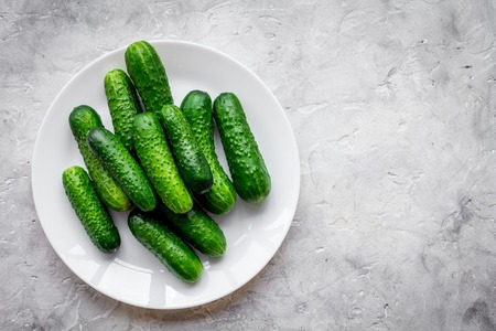 Fresh cucumbers on plate on grey top view copyspace