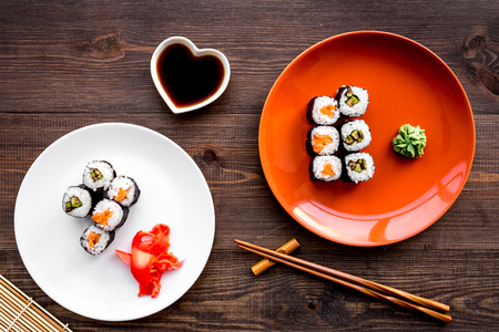 Sushi roll with salmon and avocado on plate with soy sauce, chopstick, wasabi on wooden table top view