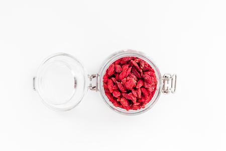 白い背景上から見る copyspace のガラスの瓶に goji の果実を乾燥させた