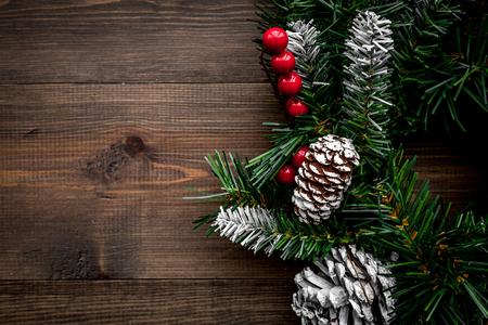 Weihnachtskranz gesponnen von den Fichtenzweigen mit roten Beeren auf Draufsichtspottbild des hölzernen Hintergrundes Standard-Bild - 89064640