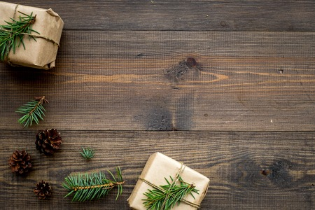 Gifts for new year wrapped in craft paper near spruce branches and cones on wooden background top view pattern copyspace Banco de Imagens