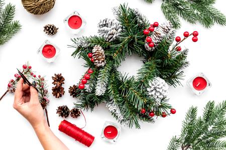 Machen Sie Weihnachtskranz. Hand halten Sciccor nahe gesponnenen Fichtenzweigen, Kegel, Threads auf Draufsicht des weißen Hintergrundes Standard-Bild - 89287939