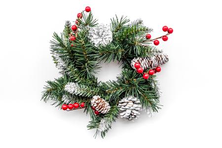 Weihnachtskranz gesponnen von den Fichtenzweigen mit roten Beeren auf Draufsicht des weißen Hintergrundes Standard-Bild - 89287951