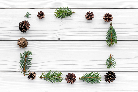 New year symbols pattern. Spruce branches and cones on white wooden top view copyspace