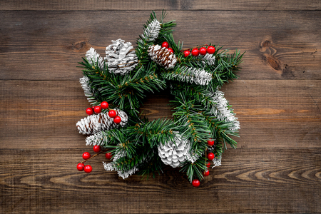 Christmas wreath woven of spruce branches with red berries on wooden top view