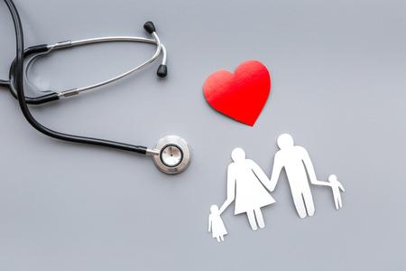 Saca salud para la familia. Estetoscopio, corazón de papel y silueta de la familia en la vista superior gris Foto de archivo - 88971360