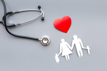 Take out health for family. Stethoscope, paper heart and silhouette of family on grey top view Stock Photo