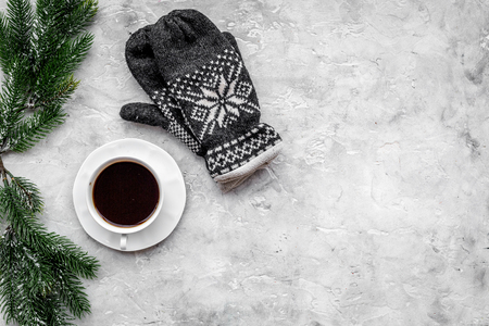Cozy christmas evening. Coffee and knitten mittens on grey stone top view copyspace Stock Photo