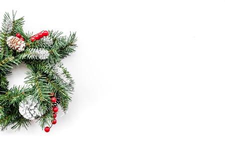 Weihnachtskranz gesponnen von den Fichtenzweigen mit roten Beeren auf weißes Draufsicht copyspace Standard-Bild - 88971364