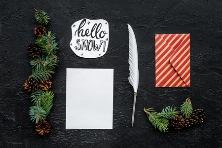Write greetings. Envelope, paper, pen, hello snow hand lettering on black background top view pattern