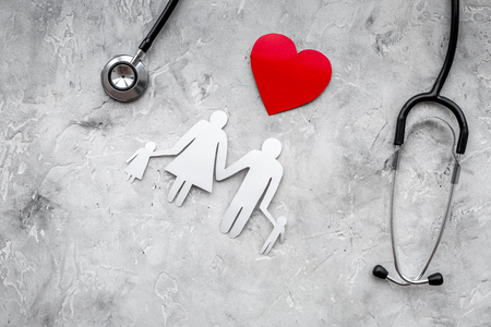 Take out health for a family. Stethoscope, paper heart and silhouette of family on grey stone top view copy space
