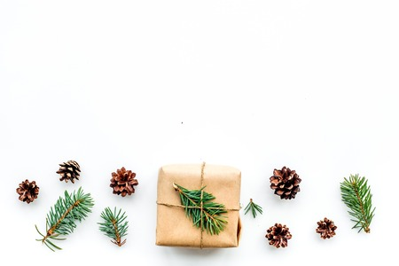 Gifts for new year wrapped in craft paper near spruce branches and cones on white top view copyspace Stock Photo