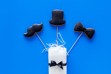 Men birthday concept. Black tie, mustache and hat cookies and goft box. Blue background top view Stock Photo