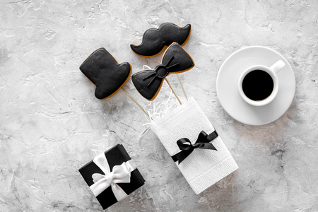 Birthday gift for men. Wrapped box, cookies in shape of black tie, mustache, hat. Grey background top view