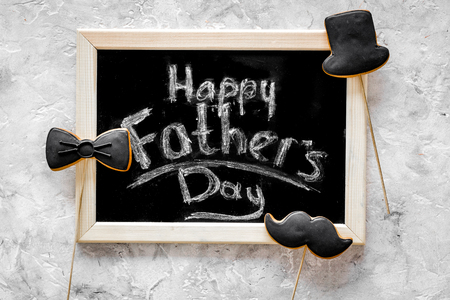 Words happy Fathers day written on blackboard. Black tie, mustache and hat cookies. Grey stone background top view Stock Photo