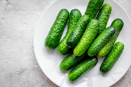Fresh cucumbers on plate on grey background top view.