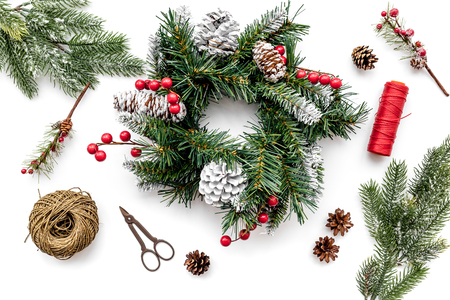 Machen Sie Weihnachtskranz. Gezierte Zweige, Kegel, Threads, Sciccors auf Draufsicht des weißen Hintergrundes. Standard-Bild - 89064575