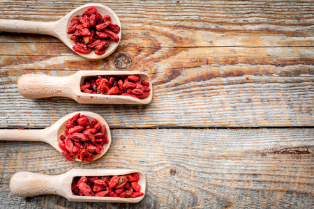 Wooden spoons with dried goji berries on wooden background top view copyspace Stock Photo